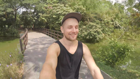 Young Hipser Man Riding Bicycle and Making Gopro Selfie in Park. HD Footage