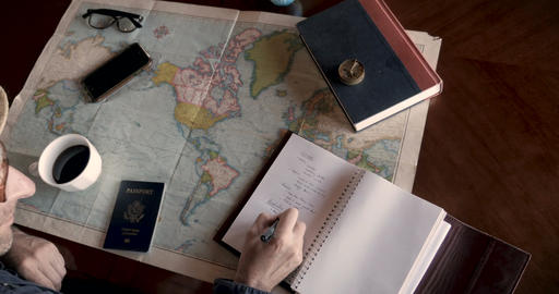 Hipster man finding places on map and writing top tourist destinations for Live Action