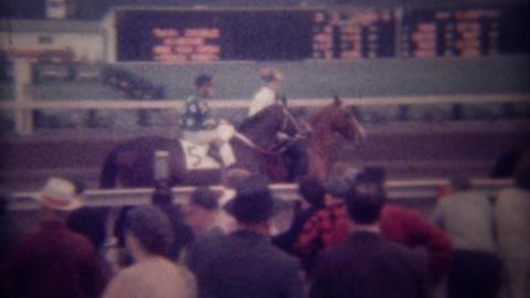 1949: Spectators watch racetrack horse jockeys walk to starting line Footage