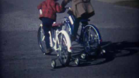 1962: Kids riding new oversized adult sized training wheel bikes Footage