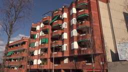 Red residential building facade with many balcony, camera pan to street view Footage