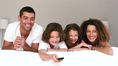 Cute family watching tv and changing channels lying on their bed Footage