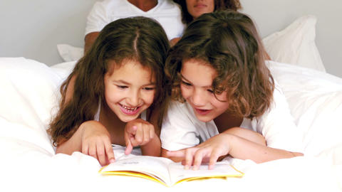 Cute siblings reading a book on their parents bed Footage