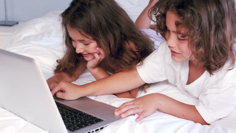 Cute siblings using laptop on their parents bed Live Action