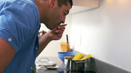 Cute couple cooking in the kitchen and man tasting the sauce Footage