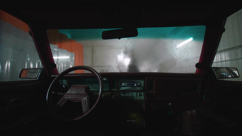 A worker at a car wash washes a car Footage