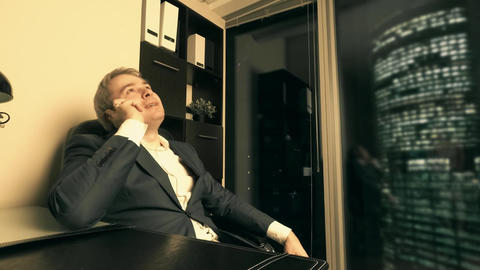 Businessman talking on his cell phone in the office in downtown in the evening Footage