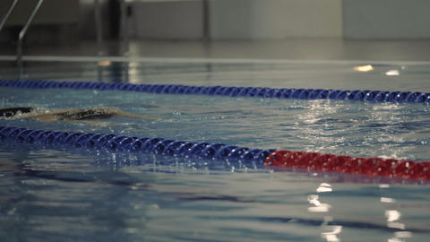 Young woman in goggles swimming breaststroke in blue water swimming pool Live Action