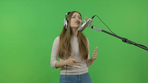 The white girl emotionally sings into the studio microphone. Record a music clip Footage