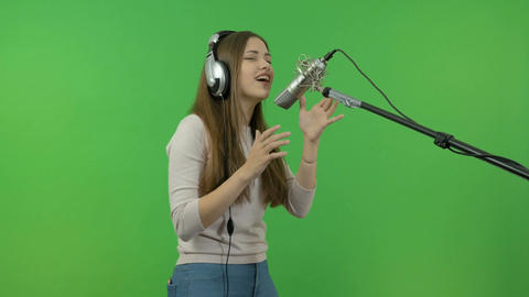 A young girl is singing into a studio microphone. On a green background Footage
