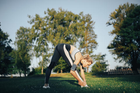 Woman doing yoga exercises in the park フォト