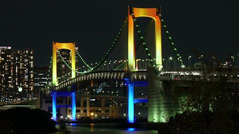 Traffic over the multi colored rainbow bridge and city lights Footage