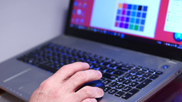 Man typing on laptop keyboard, changing color of desktop background Footage