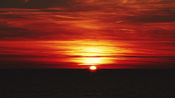 Beautiful red sunset over the sea with red clouds, the sun disappears behind the Footage