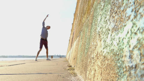Young Man Raises Hands And Dances on a Riverbank With a High Wall in Slo-Mo Footage