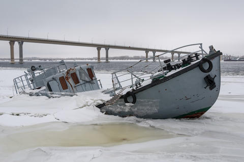 Sinking boat in a frozen river Photo