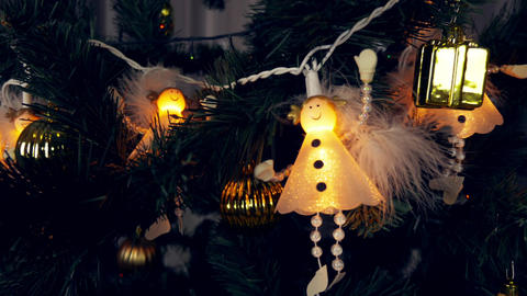 Electrogarlands of white angels are hanging on a Christmas tree. Beautiful cute 画像