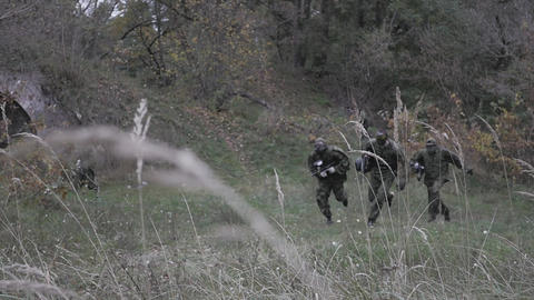 hree men of paintball players run in the forest in slow motion Footage