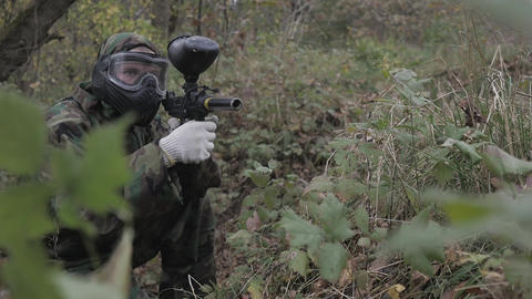 Paintball player in grass shoots in slow motion Footage