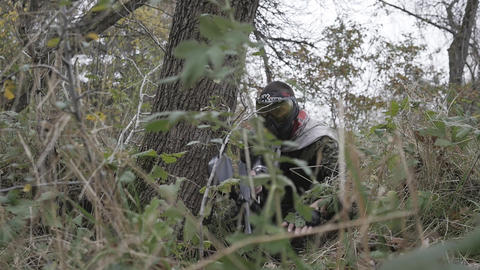 Paintball player crawling on plastunno slow-motion shooting Footage