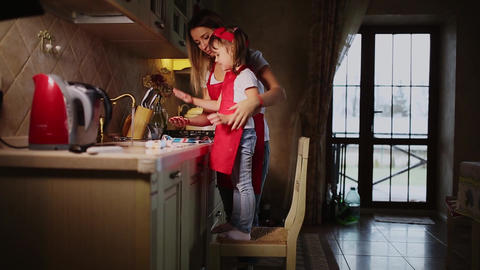 Mom helps to wash the hands of his daughter in the kitchen after cooking dinner Footage