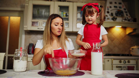 Beautiful young mother helping her little daughter along to cook cake in red Footage
