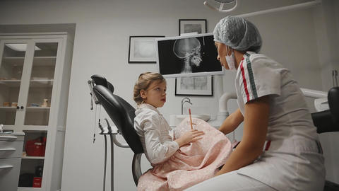 Office dentist orthodontist dentist shows x-ray images of the teeth and holds Live Action