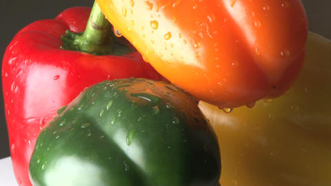Rotating red orange yellow and green bell peppers zoomed out Footage