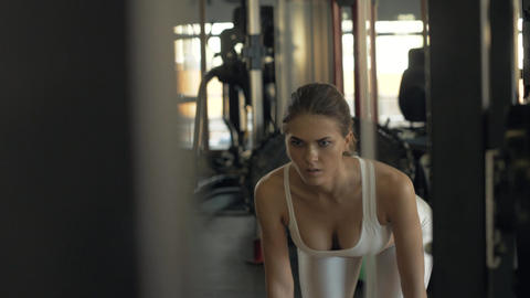 Sexy woman making incline with barbell and looking in mirror on gym club Footage