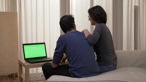 Smiling couple sitting on the edge of the bed looking at a laptop with green Footage