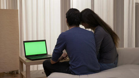 Happy couple sitting on the sofa with a laptop watching a movie kissing and Footage
