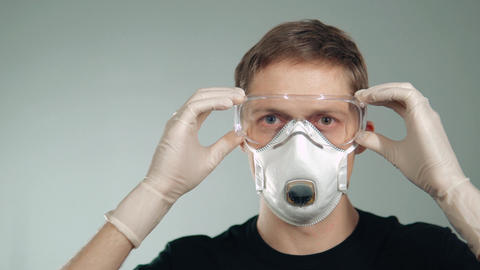protective mask on the face. a man puts on his glasses. protection of the Footage