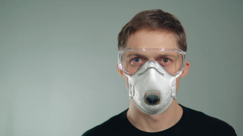 protective mask on the face. a man puts on his glasses.... Stock Video Footage