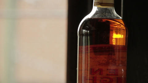 Reflections in still whiskey bottle Footage
