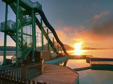 Sunset shore and toboggan slides at lake,. High ladder tower with sliding track Photo