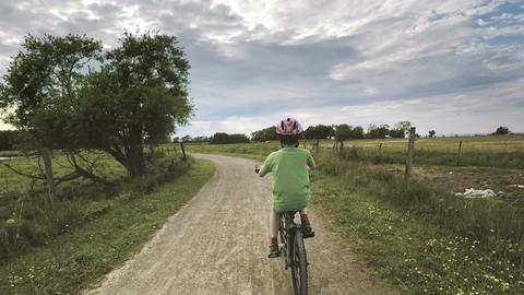 Child riding bicycle on rural road Footage