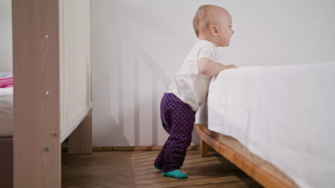 Baby Standing near the bed at Home フォト