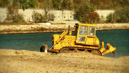 Yellow Bulldozer tractor lifts sand on the beach ビデオ