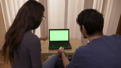 Young happy couple booking online vacation using a laptop with green screen Footage