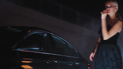 Beautiful blonde posing in a black dress at night near a car Footage