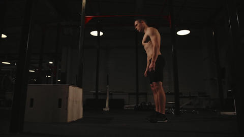 Muscular man shirtless performs the burpee exercise and jump up on a wooden box Footage