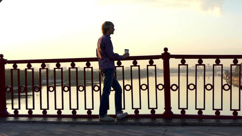 Romantic Man Drinks Coffee And Enjoys a Sunset on a Bridge in Slo-Mo Footage