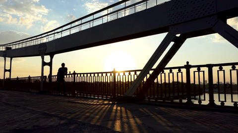 Young Man Relaxes, Drinks Coffee And Enjoys a Sunset on a Bridge in Slo-Mo Footage