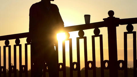 Man Drinks Coffee From a Paper Cup And Enjoys a Sunset on a Bridge in Slo-Mo Footage
