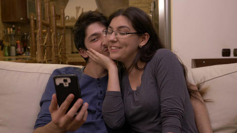 Happy affective couple sitting on the couch at home video chatting with friends Footage