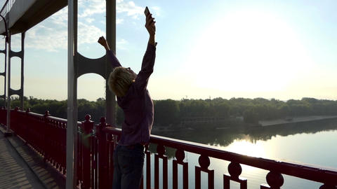 Man Stands on The Bridge, Calls, Raises His Hands Happily at Sunset in Slo-Mo Footage