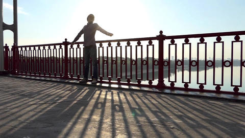 Young Man Stands Near Handrails of a Bridge Over the Dnipro at Sunset in Slo-Mo Footage