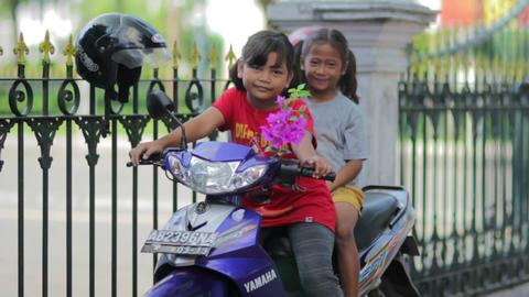 JOGJAKARTA - MAY 2012: two local kid on motorbike Stock Video Footage
