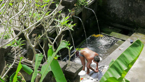 BALI - MAY 2012: balinese man washing clothes in temple Stock Video Footage