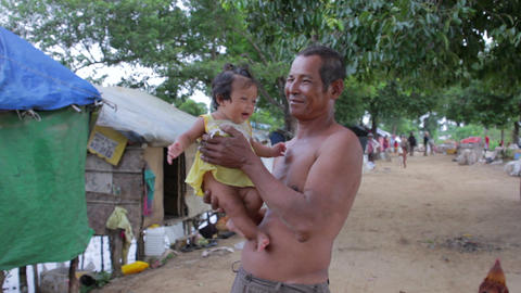Father holding baby in shanty Stock Video Footage